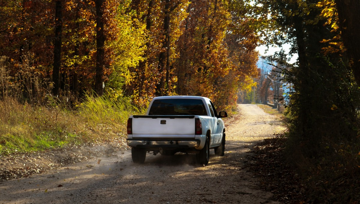 diesel truck driving down road with fall foliage